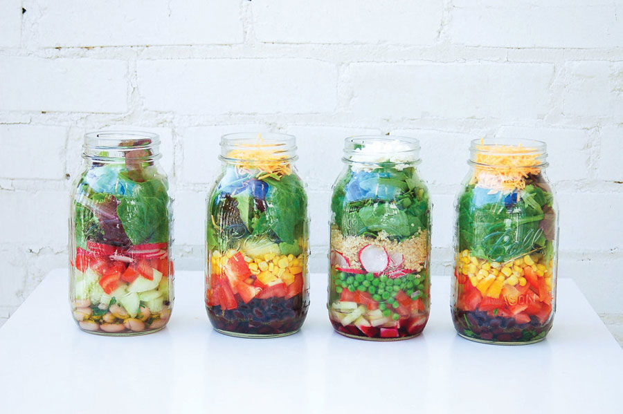 Mason jar salade: groene bladgroente, sla en kaas bovenop.