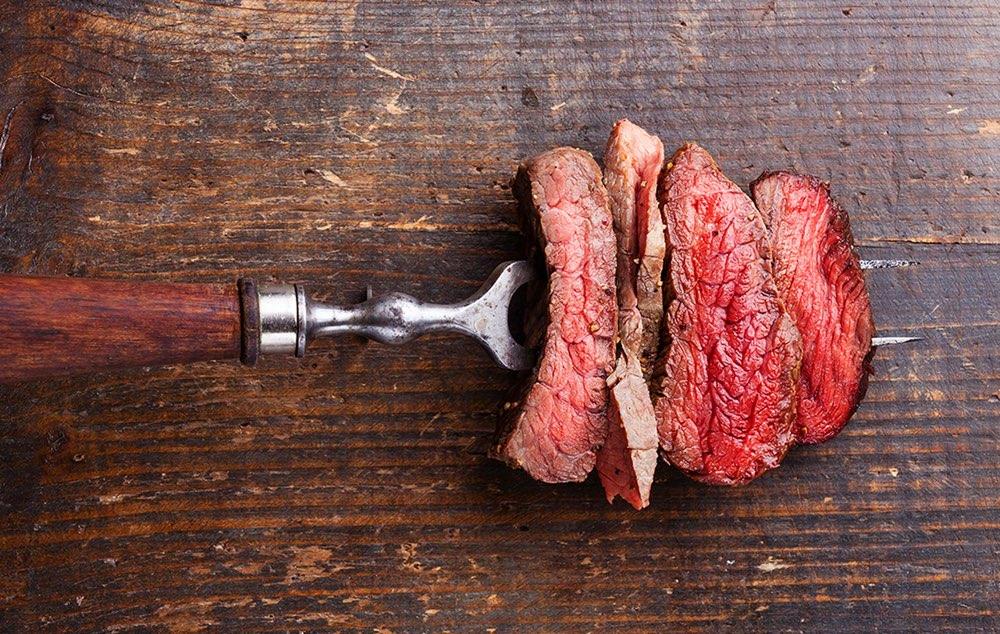 Houten snijplank en vork met vlees